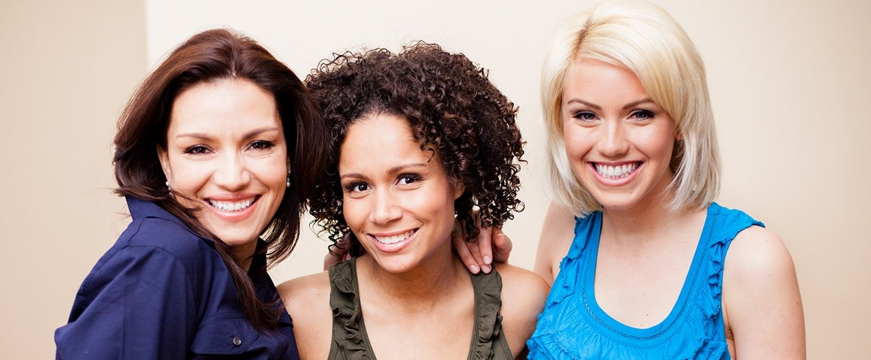 Three woman friends smiling because they have great oral health