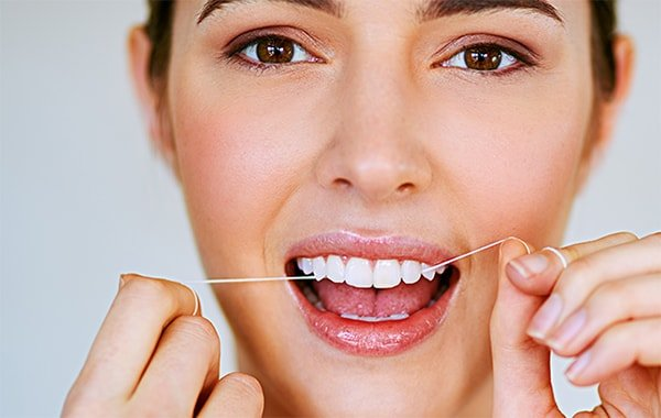 Woman practicing good oral health care by flossing