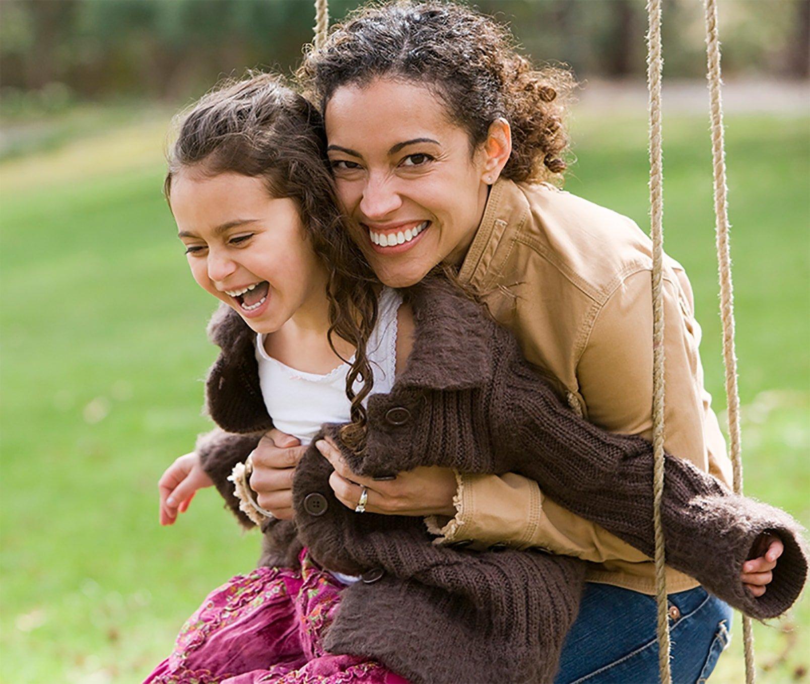 Mother swinging her daughter
