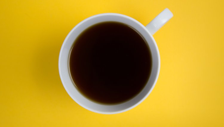 Aerial view of brown coffee in a white mug on a yellow counter