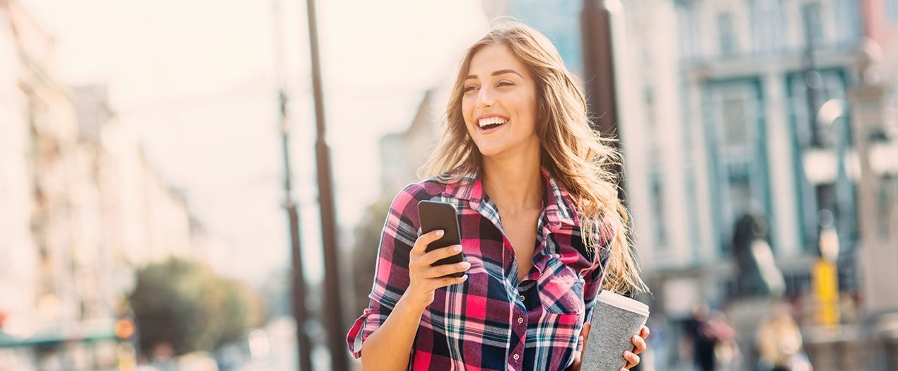 brunette woman with straight teeth wearing plaid and holding cell phone and cofffe cup