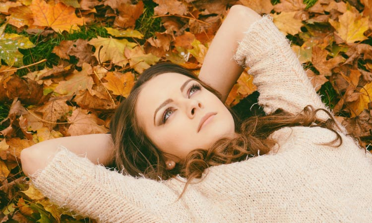 Closeup of a brunette woman wearing a sweater while lying in yellow and orange leaves thinking about her bleeding gums