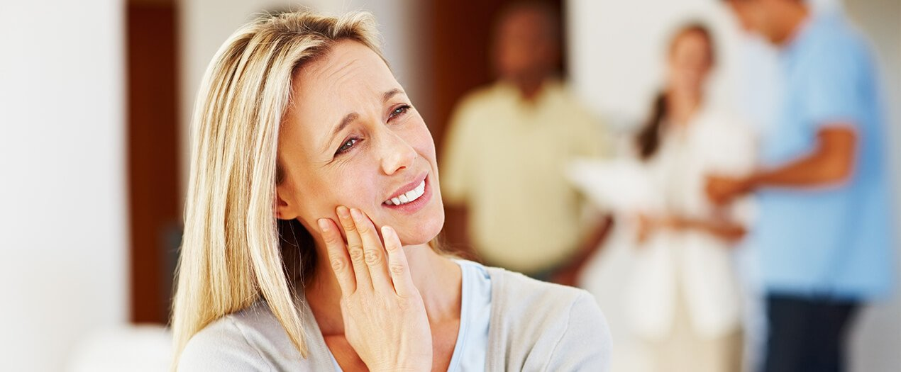 Blonde woman holding cheek because of tooth pain