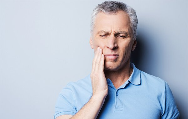 Older man with hand on face because of a toothache.