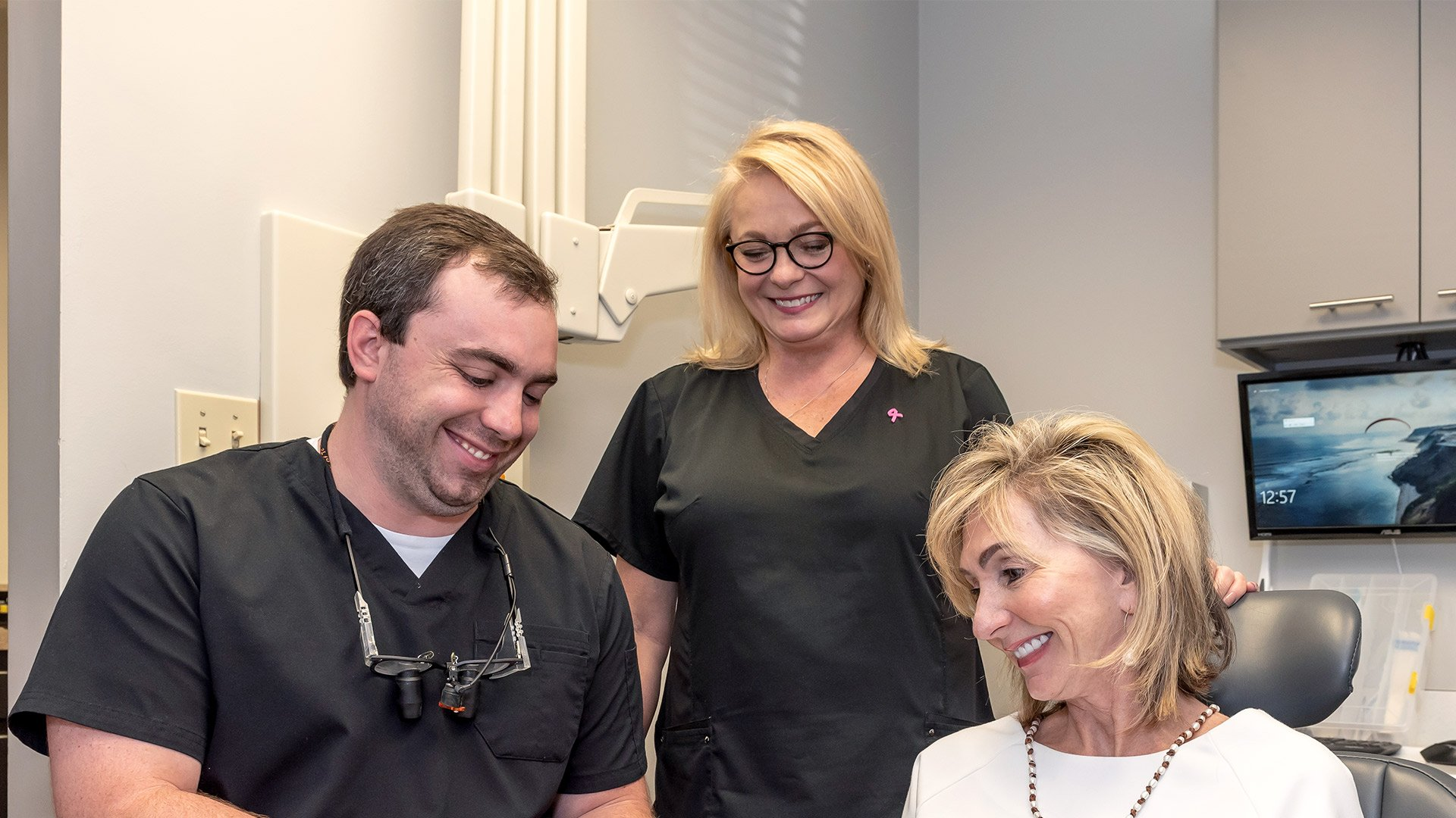 Dr. Hill and staff member smiling with senior patient